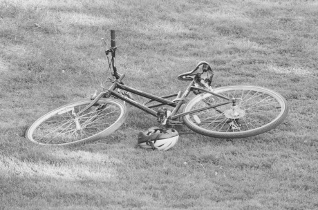 black and white photo of bicycle on its side on a lawn